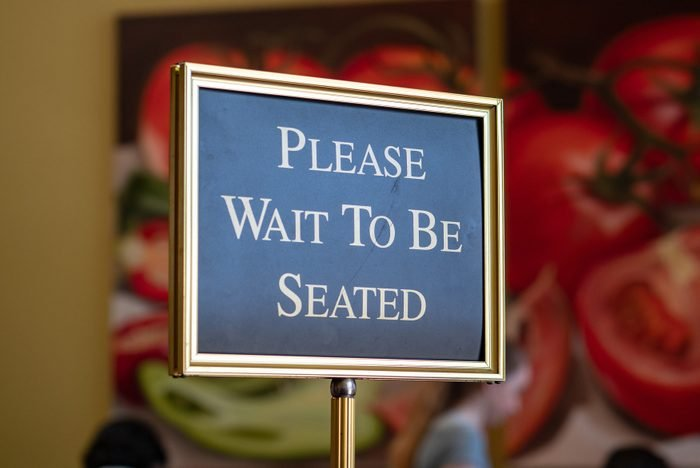 Please wait to be seated sign standing at the front of a restaurant
