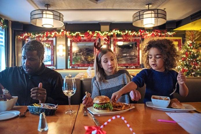 Multi-ethnic family shopping for Christmas, having a break in a restaurant