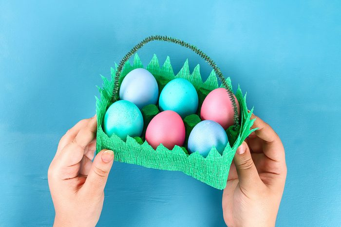 DIY basket Easter egg from cardboard tray, crepe paper, chenille stem on blue background.