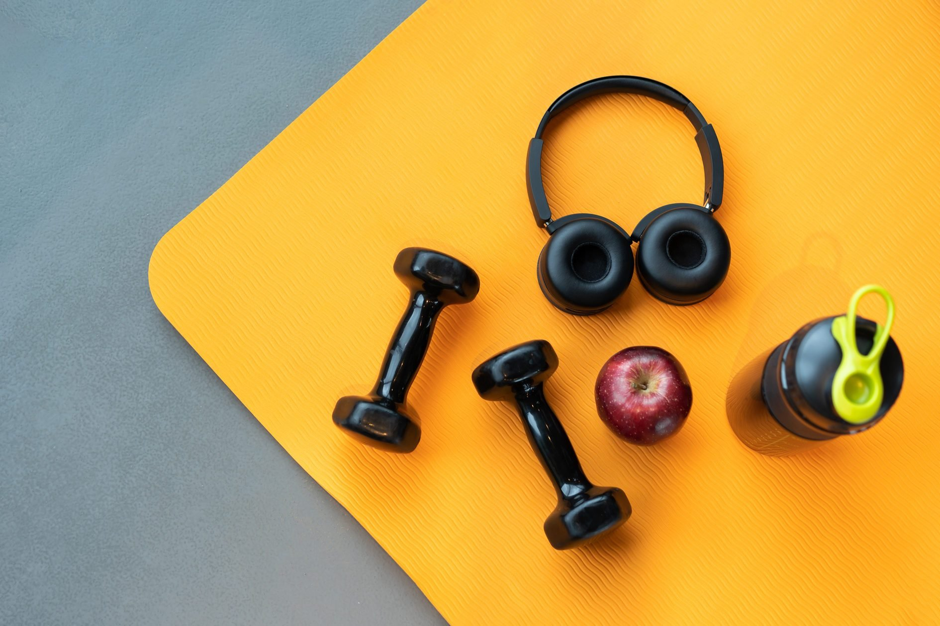 Directly Above Shot Of Apple By Dumbbell And Headphones On Mat