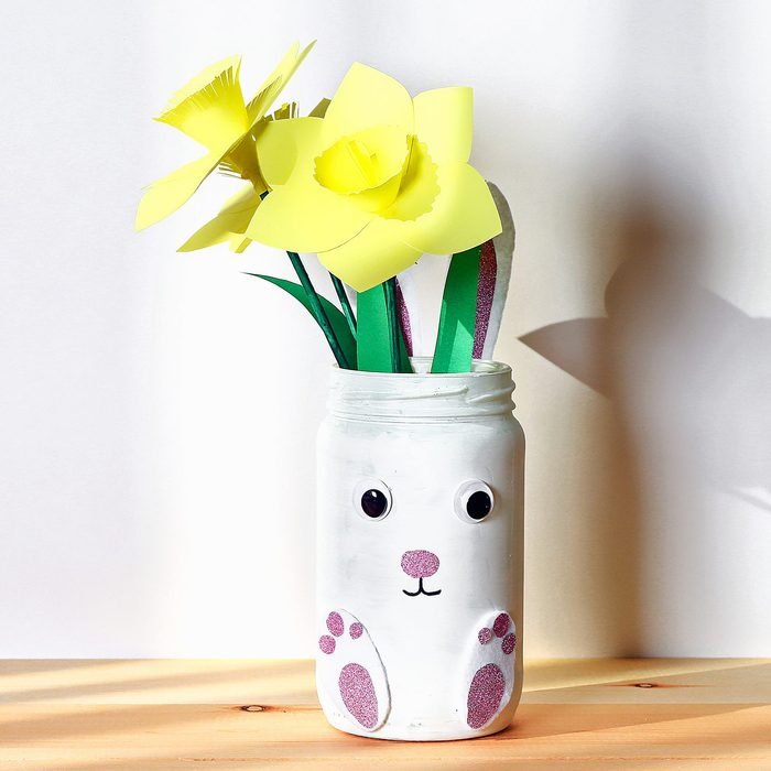 DIY Easter vase bunny with narcissus, daffodils from glass jar, felt, eyes on white wall background
