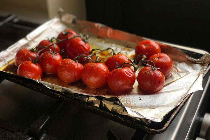 high angle view of roasted tomatoes on a pan lined with aluminum foil