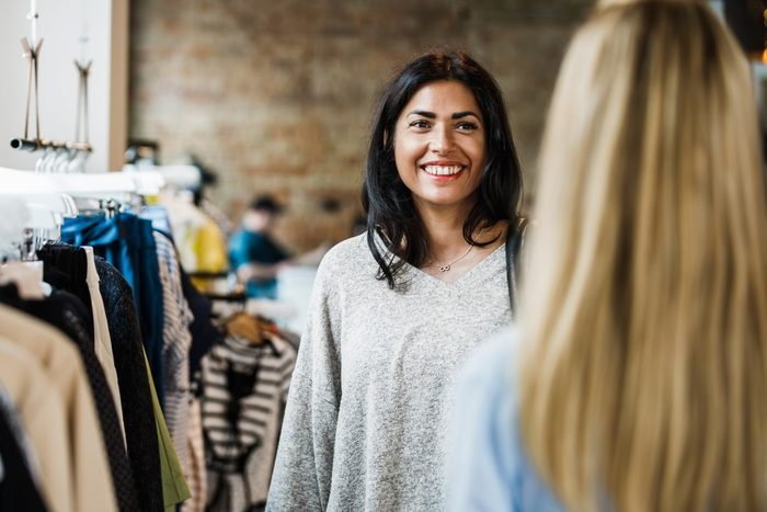 Two Friends Chatting While Shopping In Clothes Store Together