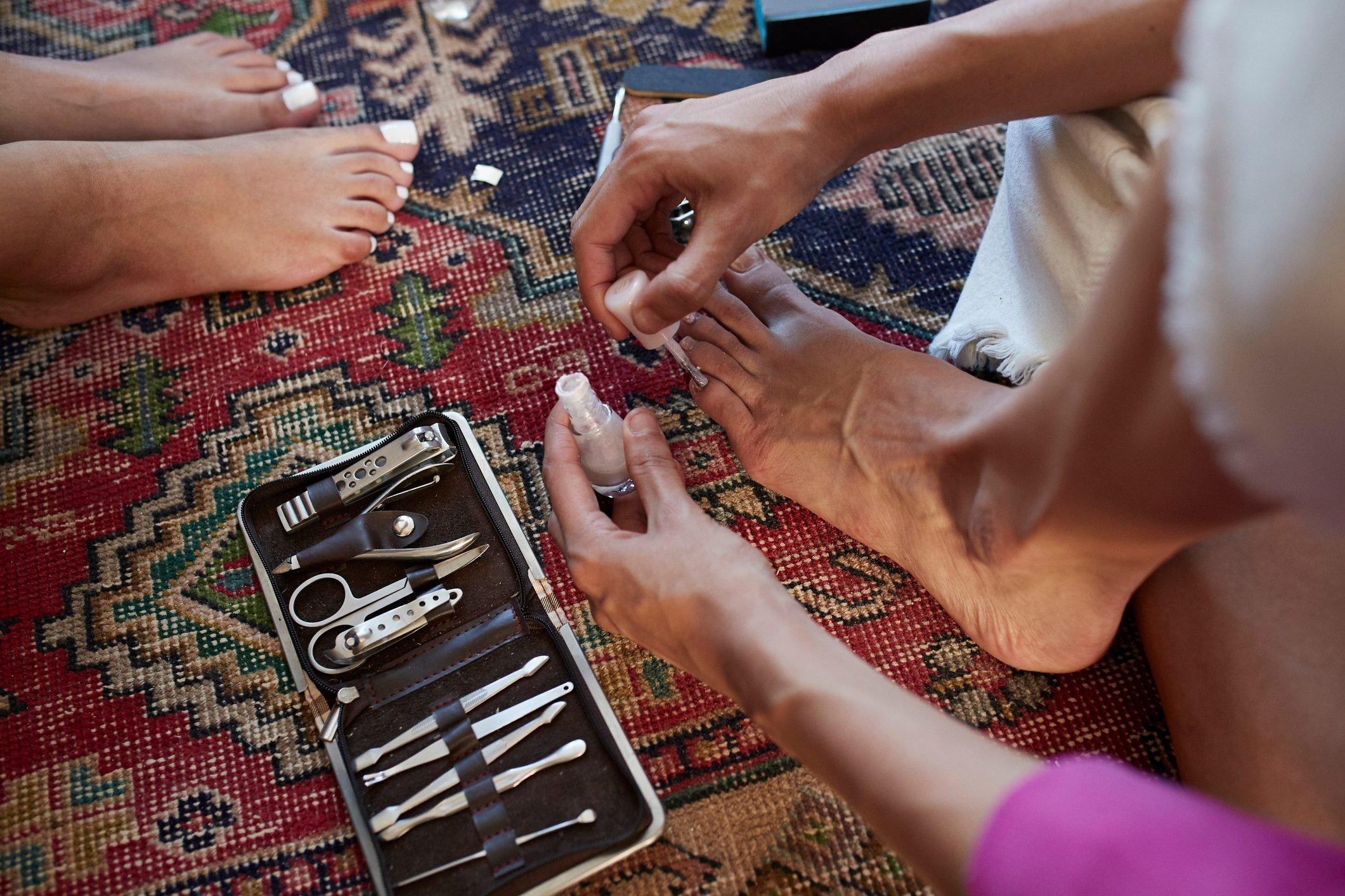 Woman applying nail polish while sitting on carpet