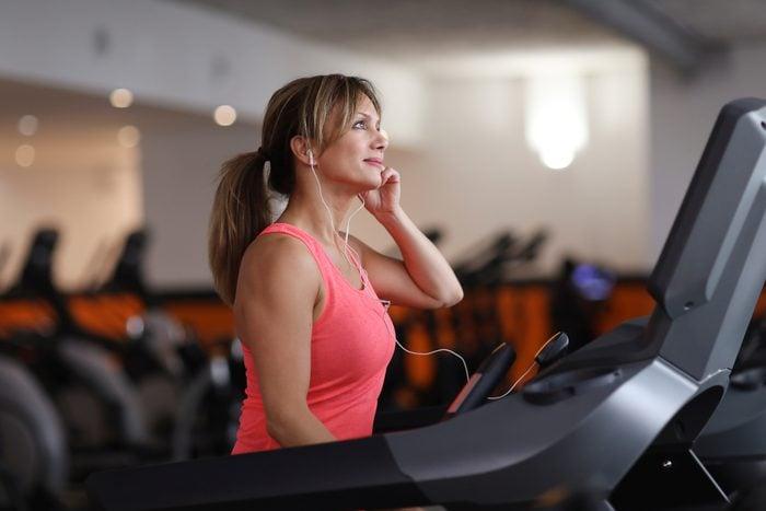Woman walking on treadmill at fitness center
