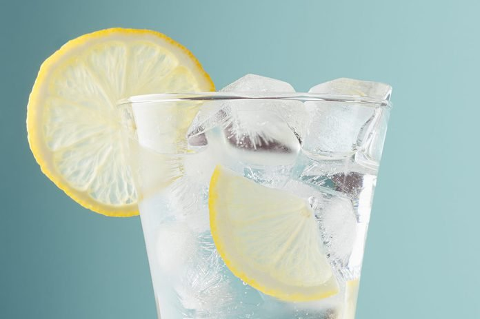Healthy fresh tonic with lemon, ice cubes, soda in misted glass on pastel green color background, closeup, half, details, top.