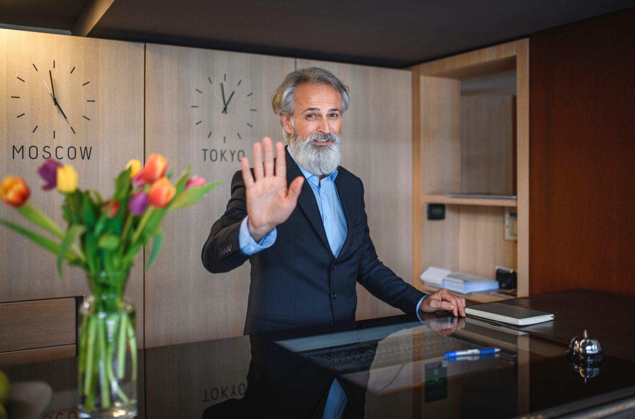 Mature Male Hotel Receptionist Bidding Guest Farewell