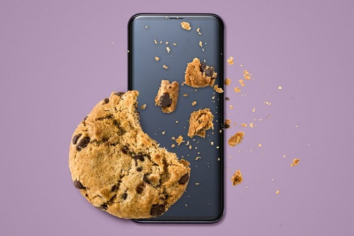 a chocolate chip cookie with crumbs on top of a smartphone on a purple background