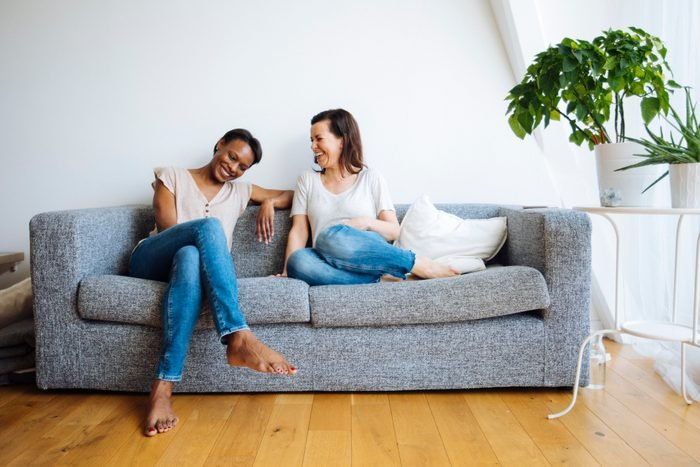 Two happy relaxed women sitting on couch at home