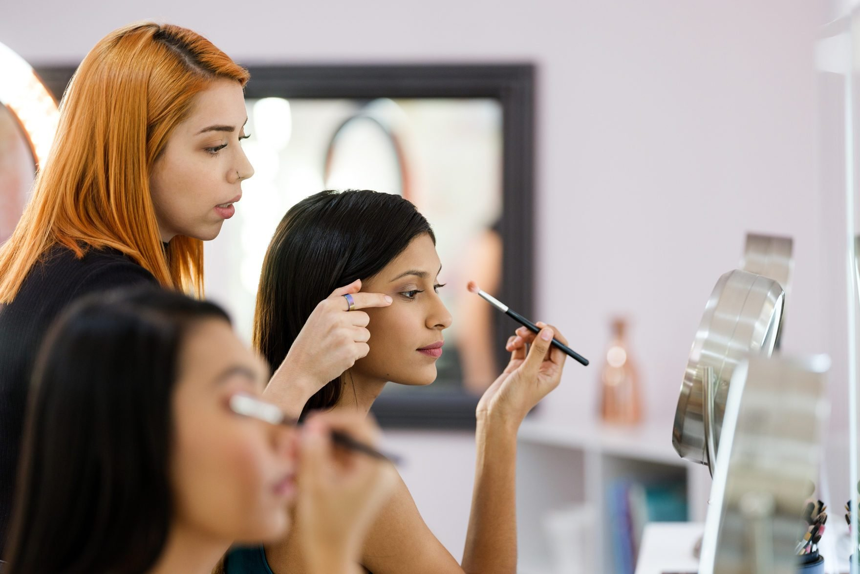 Make-up artist teaching young women about make-up