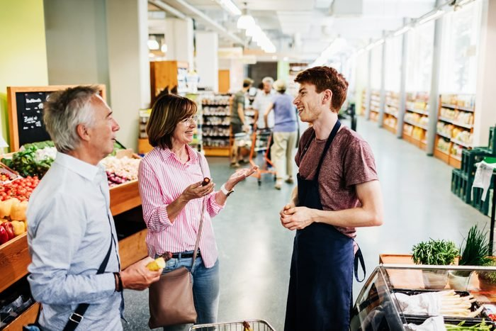 Mature Couple Speaking With Supermarket Clerk While Shopping