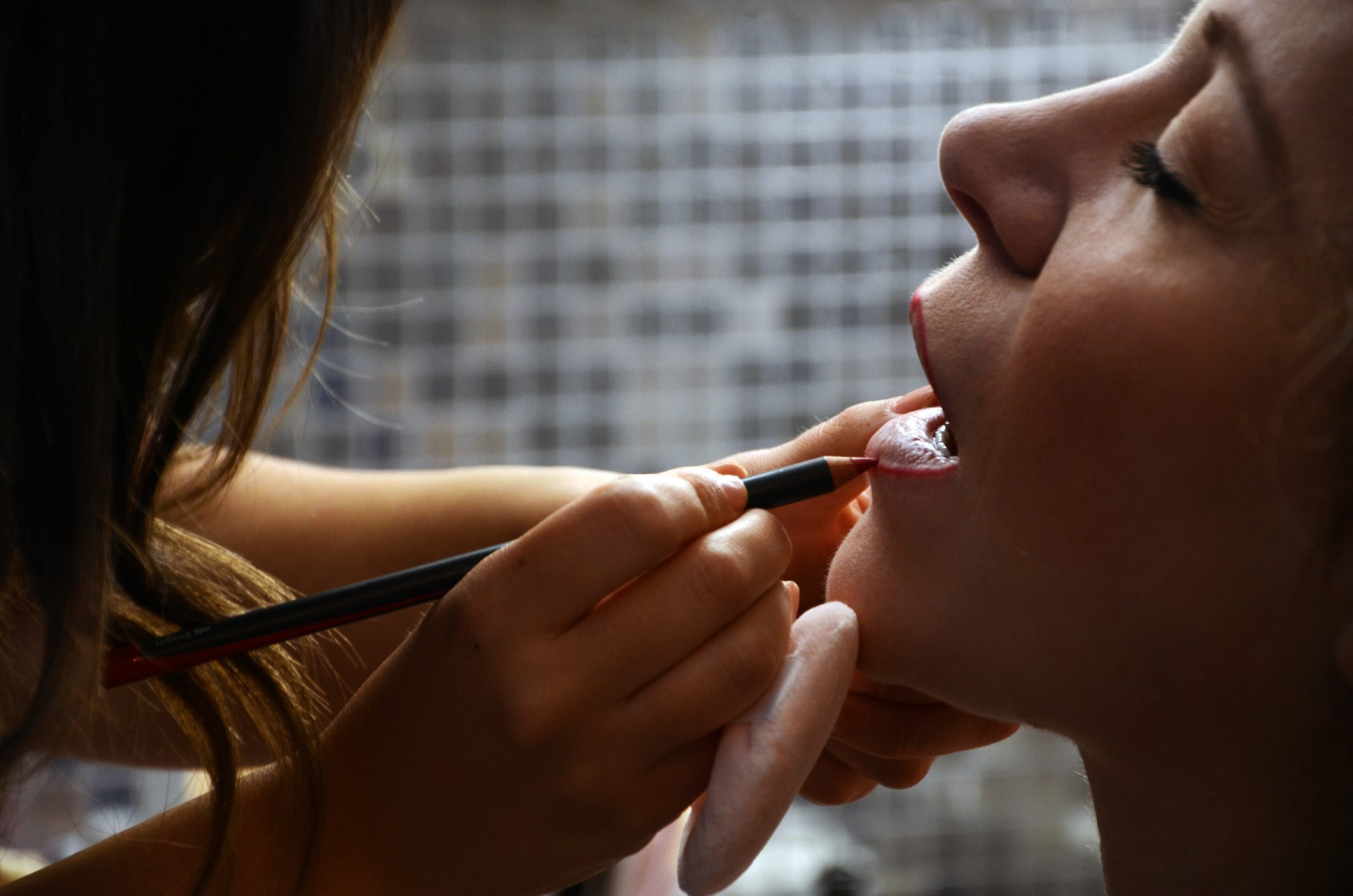 Midsection Of Make-Up Artist Applying Lip Liner To Woman In Spa