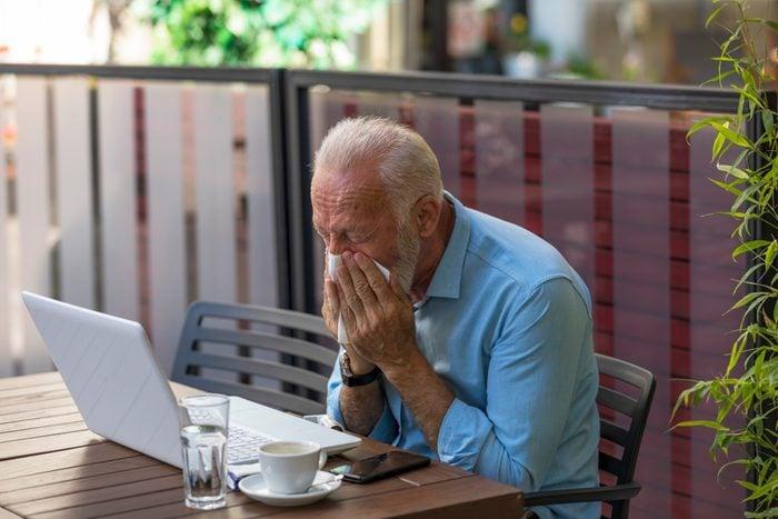 Older Man is Blowing Nose in Paper Tissues in Restaurant Garden