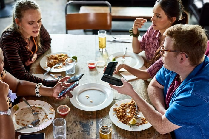 Millennial friends sharing contacts over lunch