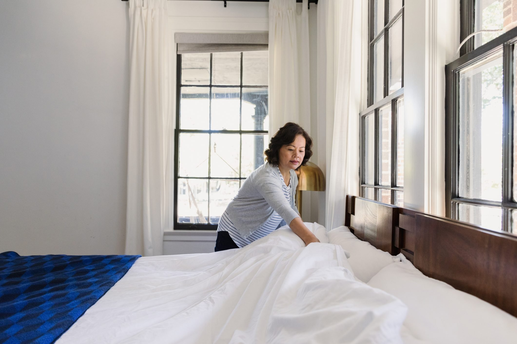 Senior woman concentrates while making her bed