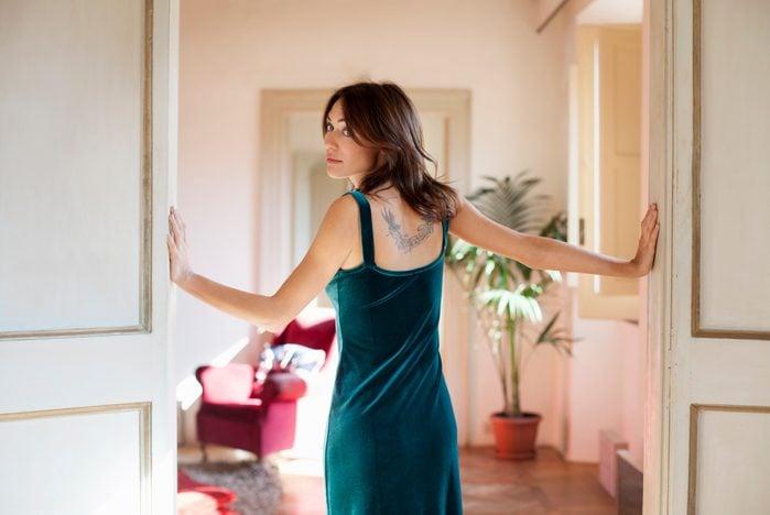 Young woman standing in doorway of elegant apartment, looking over her shoulder