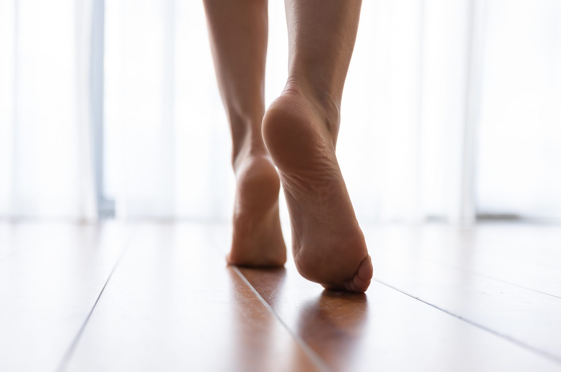 Female feet walking on warm heated floor close up view