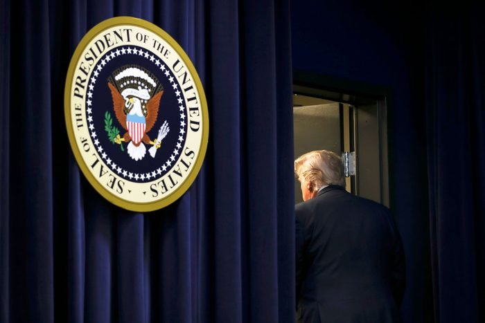 President Trump leavind through a door next to the seal of the president of the united states