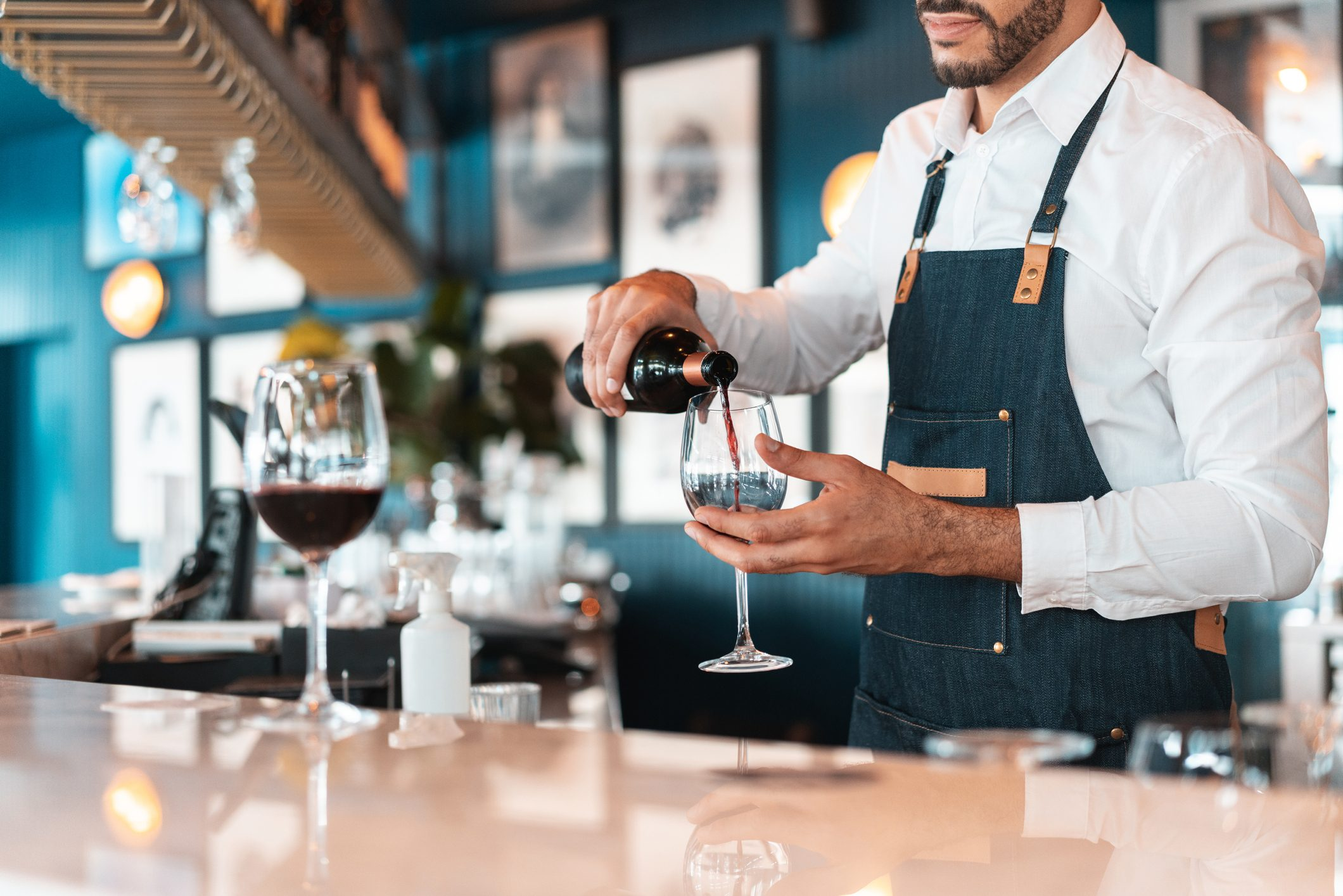 Sommelier serving red wine in luxury hotel bar