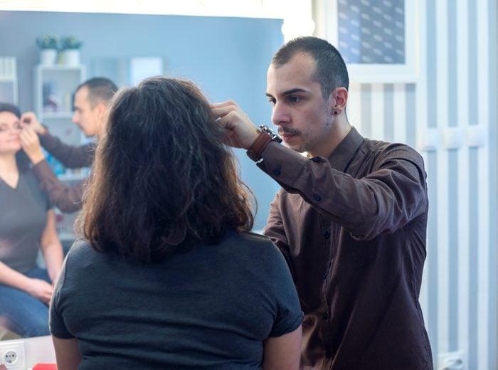 Young man,make-up artist,applying blush on young woman's cheek