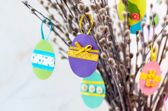 Easter eggs cutted from color paper decorated with ribbon and buttons on willow branches
