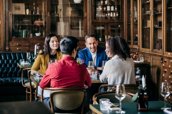 Group Of Friends Sitting At Table In Fancy Restaurant