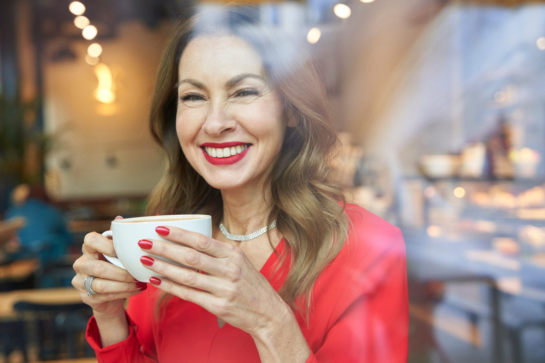 Portrait of laughing mature woman with cup of coffee behind windowpane