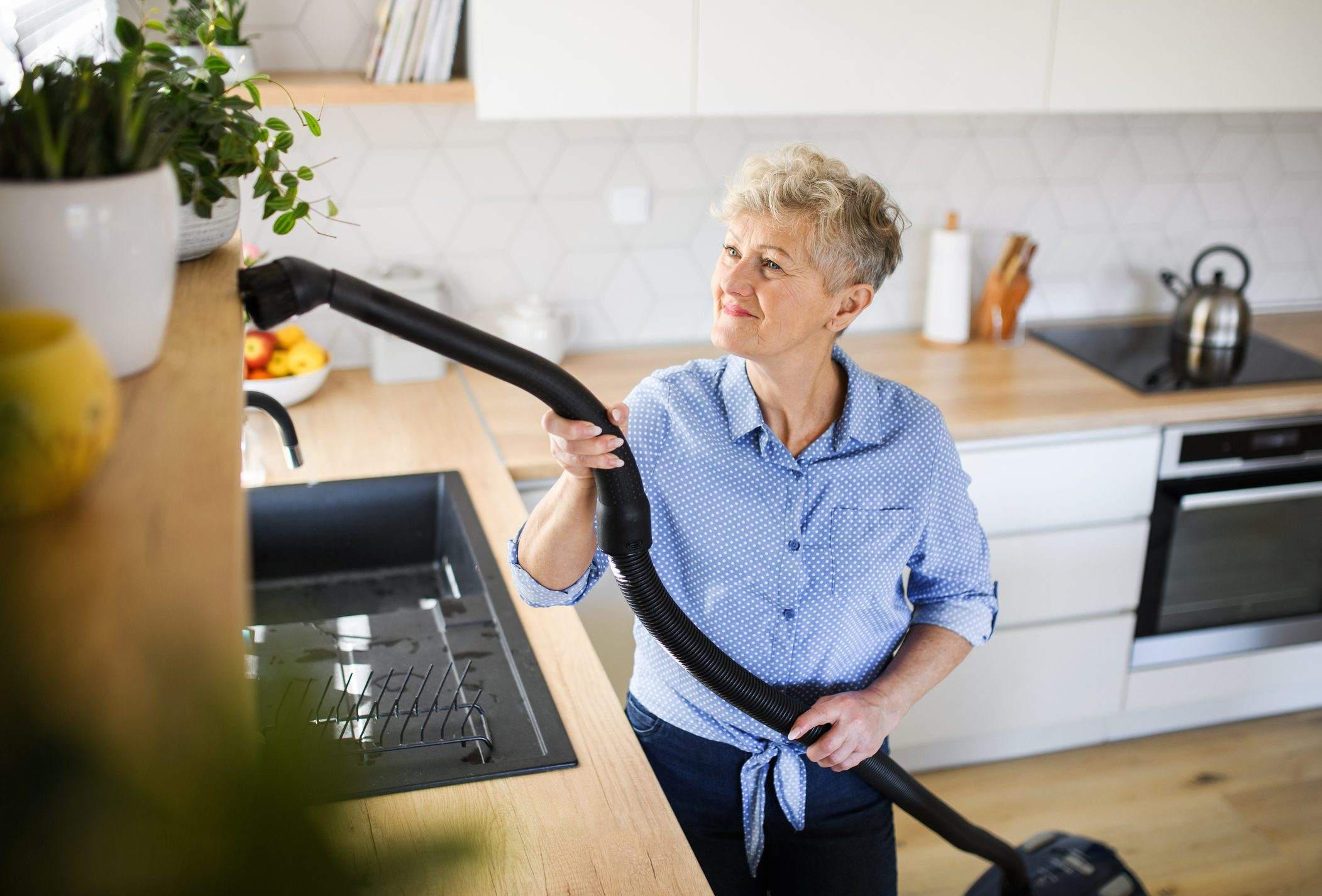 A senior woman with vacuum cleaner indoors at home, cleaning kitchen.