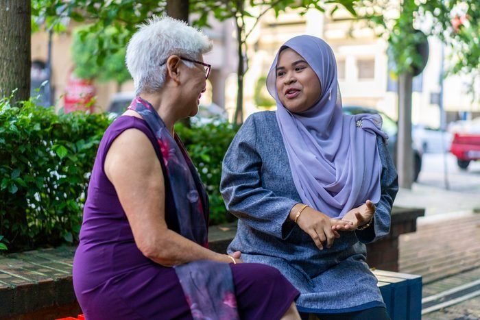 Senior Chinese lady having conversation with Malay friend outdoors