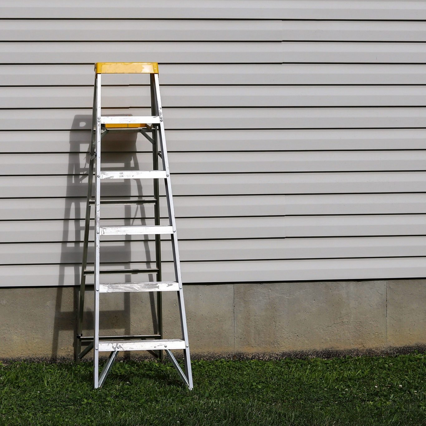 A Step Ladder Against A Side Of A Residential Home