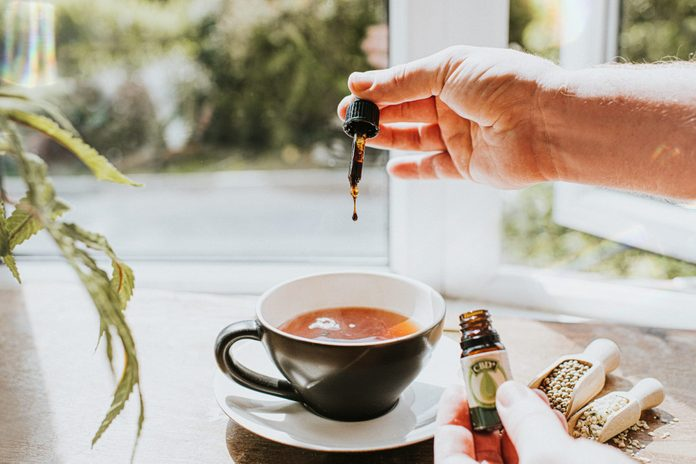 Hand Dropping Cbd Oil Into A Cup Of Tea Surrounded By Cannabis Plants