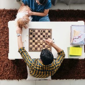 Young Man And Woman Having Fun With Dog While Playing Chess
