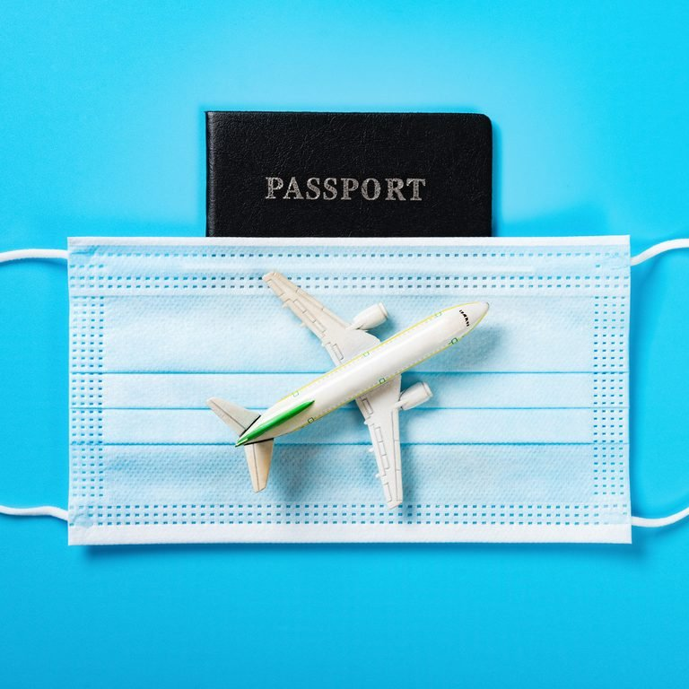 airplane model above a medical mask and a passport