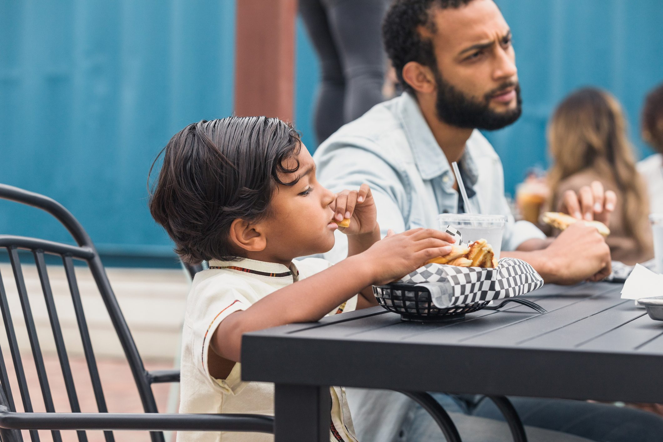 Boy eats food while dad chats at patio restaurant