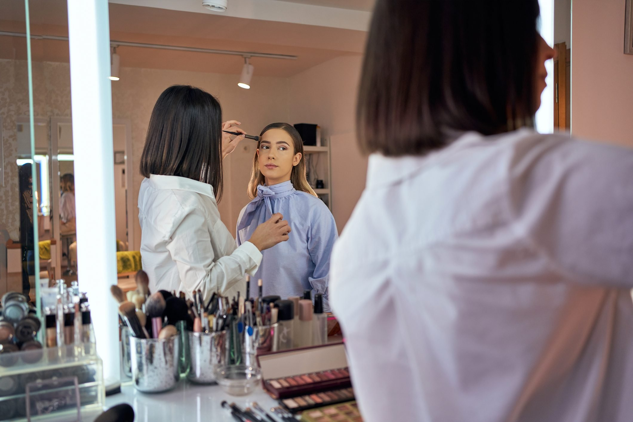 Satisfied customer looking herself in the mirror while professional make up artist using her magic