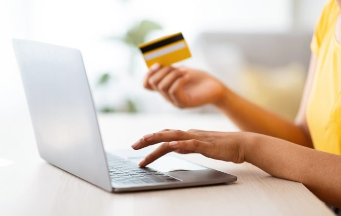 Black woman using laptop and credit card sitting at desk