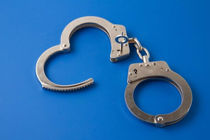 Open handcuffs on blue background