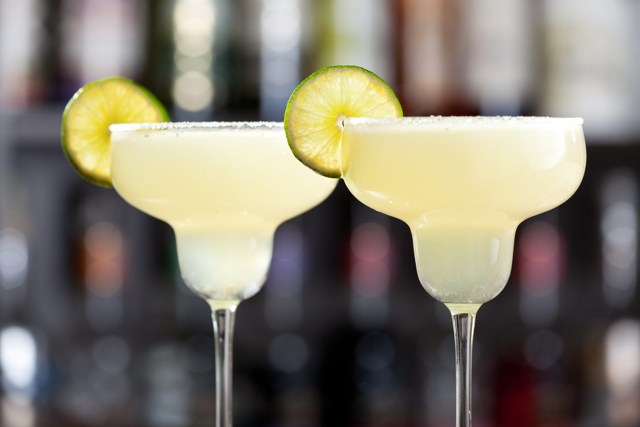 Two margaritas with lime wedges and salted glasses