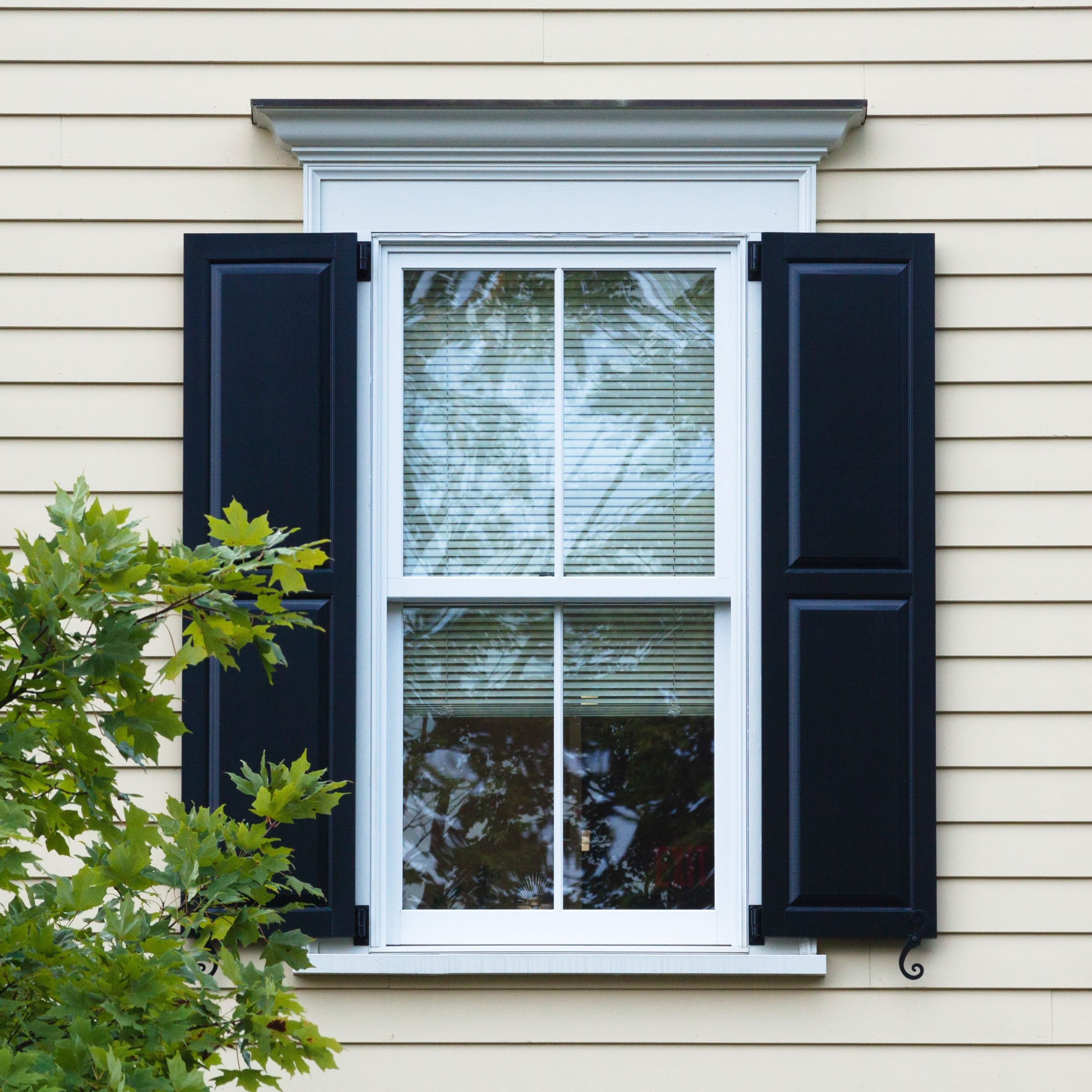 exterior shot of a window of a house with dark shutters