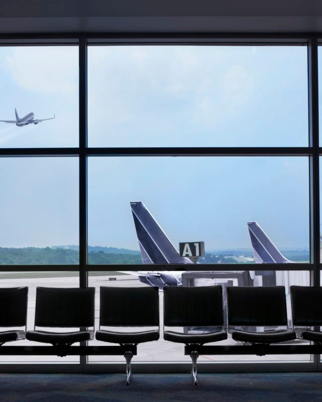 Airport waiting area, airplane taking off out the window