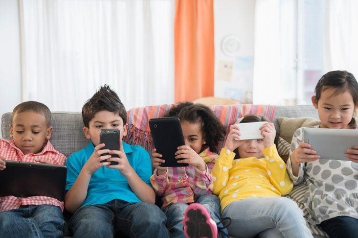 Children using technology on sofa