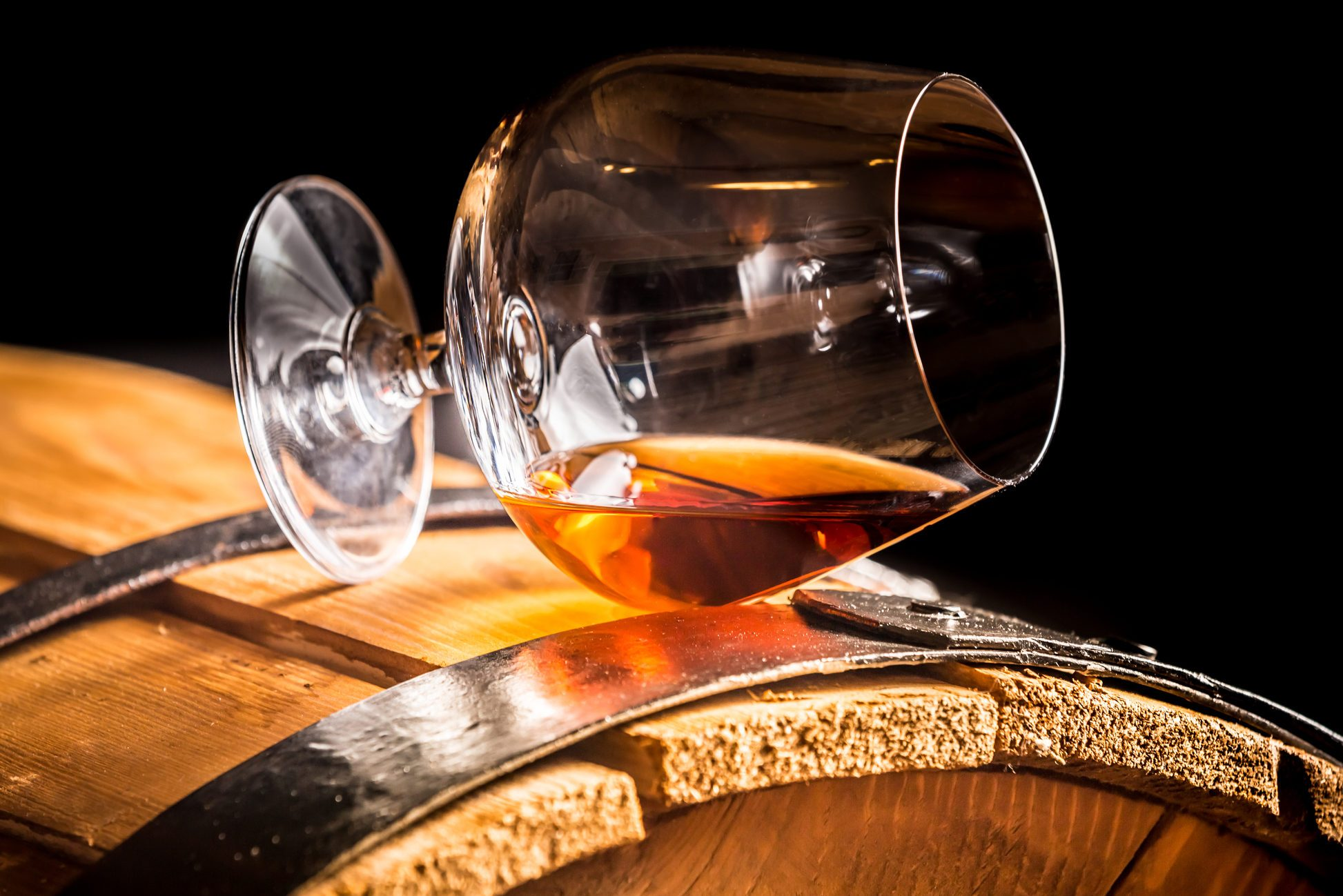 Glass of brandy on an old wooden barrel