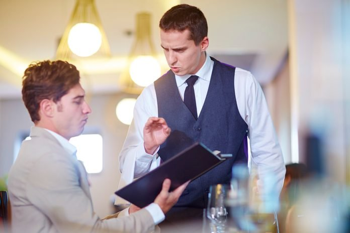 Businessman placing an order with waiter at hotel restaurant