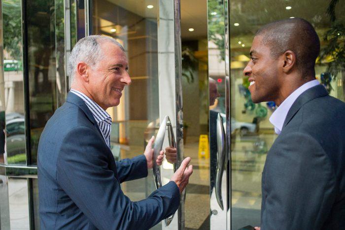 Businessman opening office door for colleague