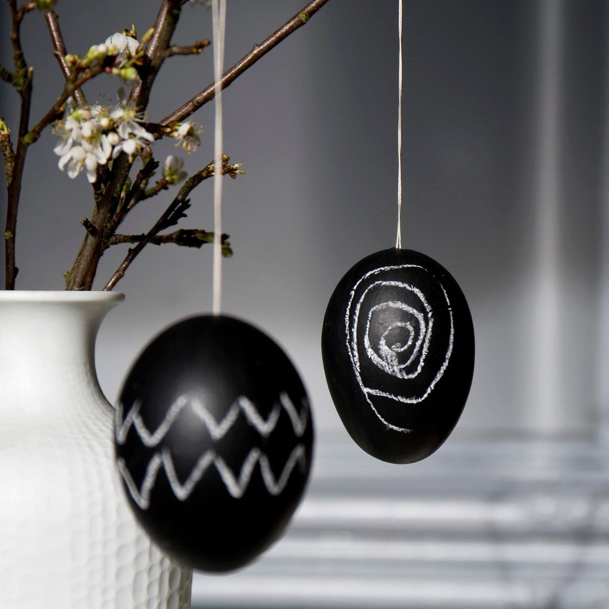Two Easter eggs painted with blackboard paint and chalk hanging on blossoming twig