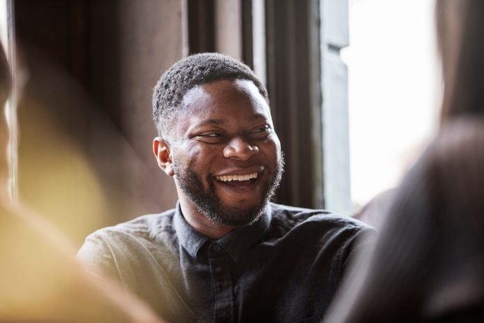 Man in a pub laughing with friends