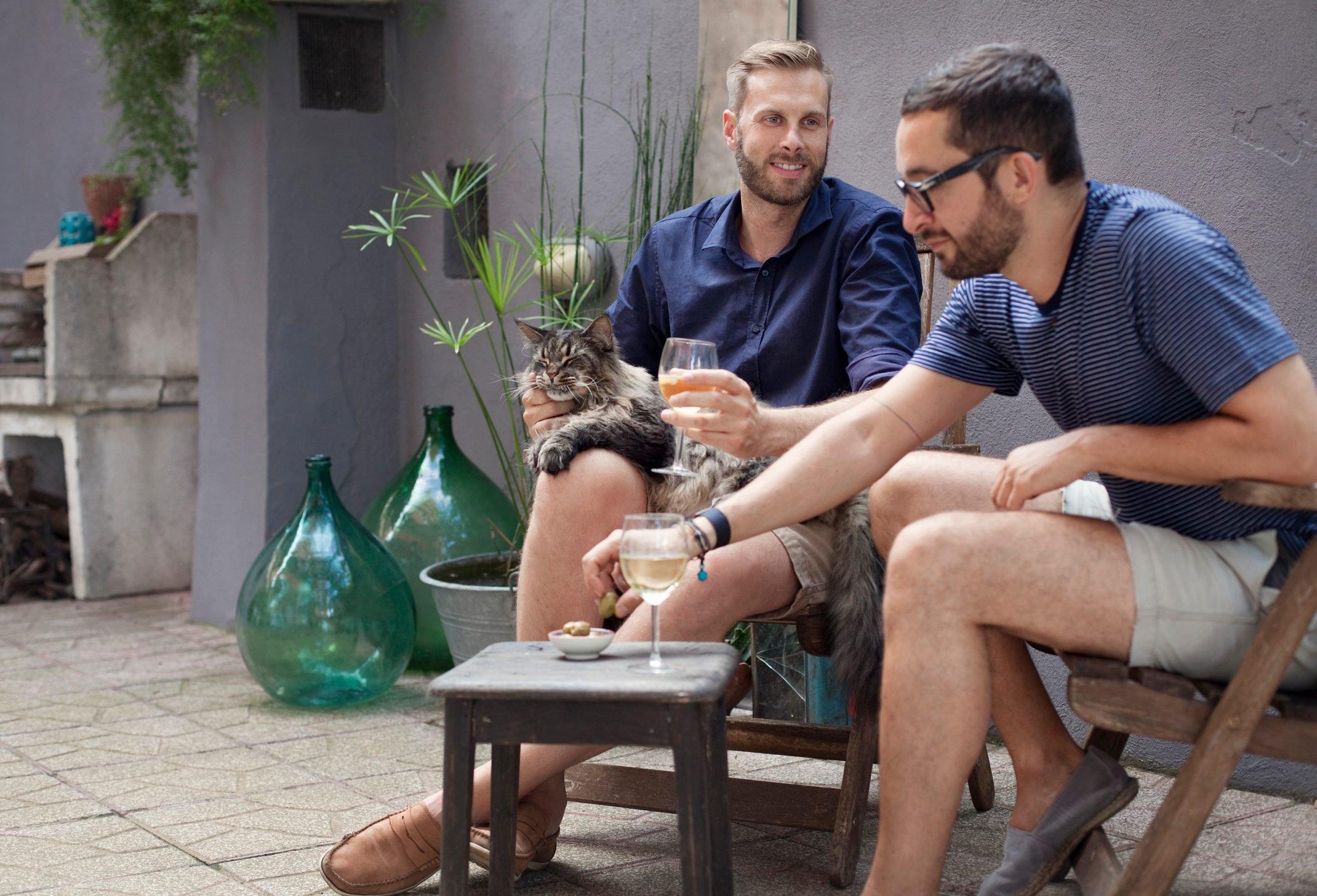 two men enjoying drinks on their terrace