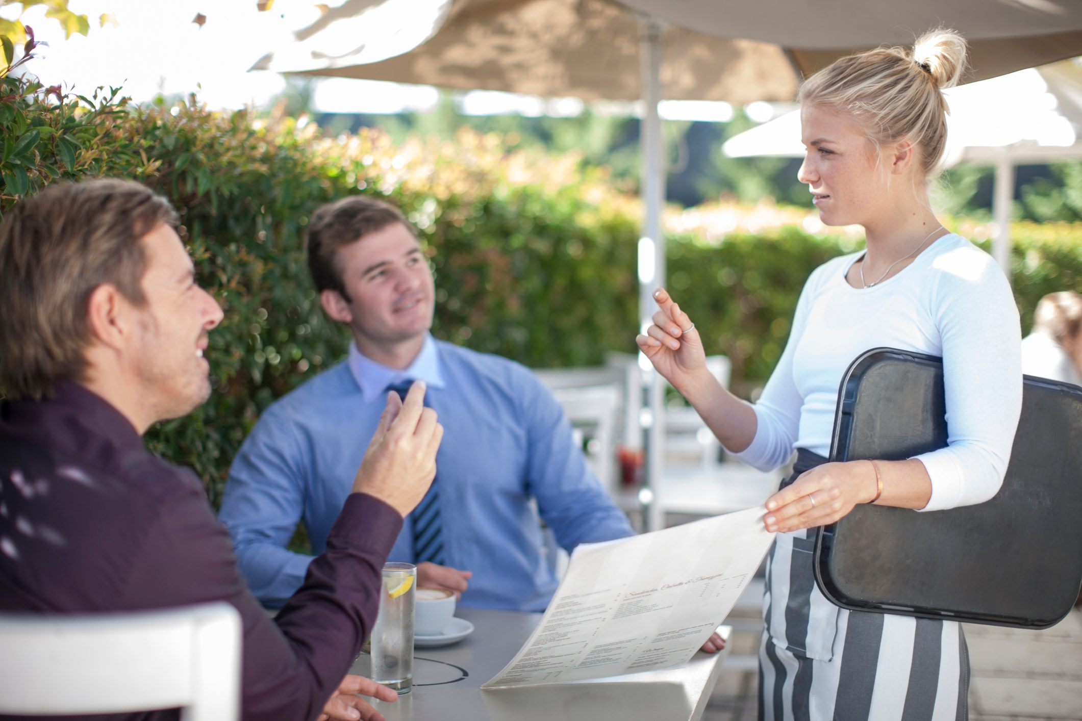 Waitress talking to two businessmen at outside restaurant