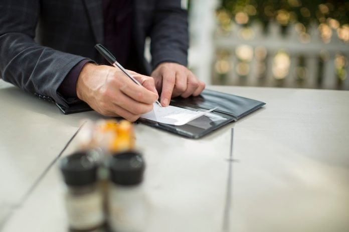 Businessman signing the bill at restaurant