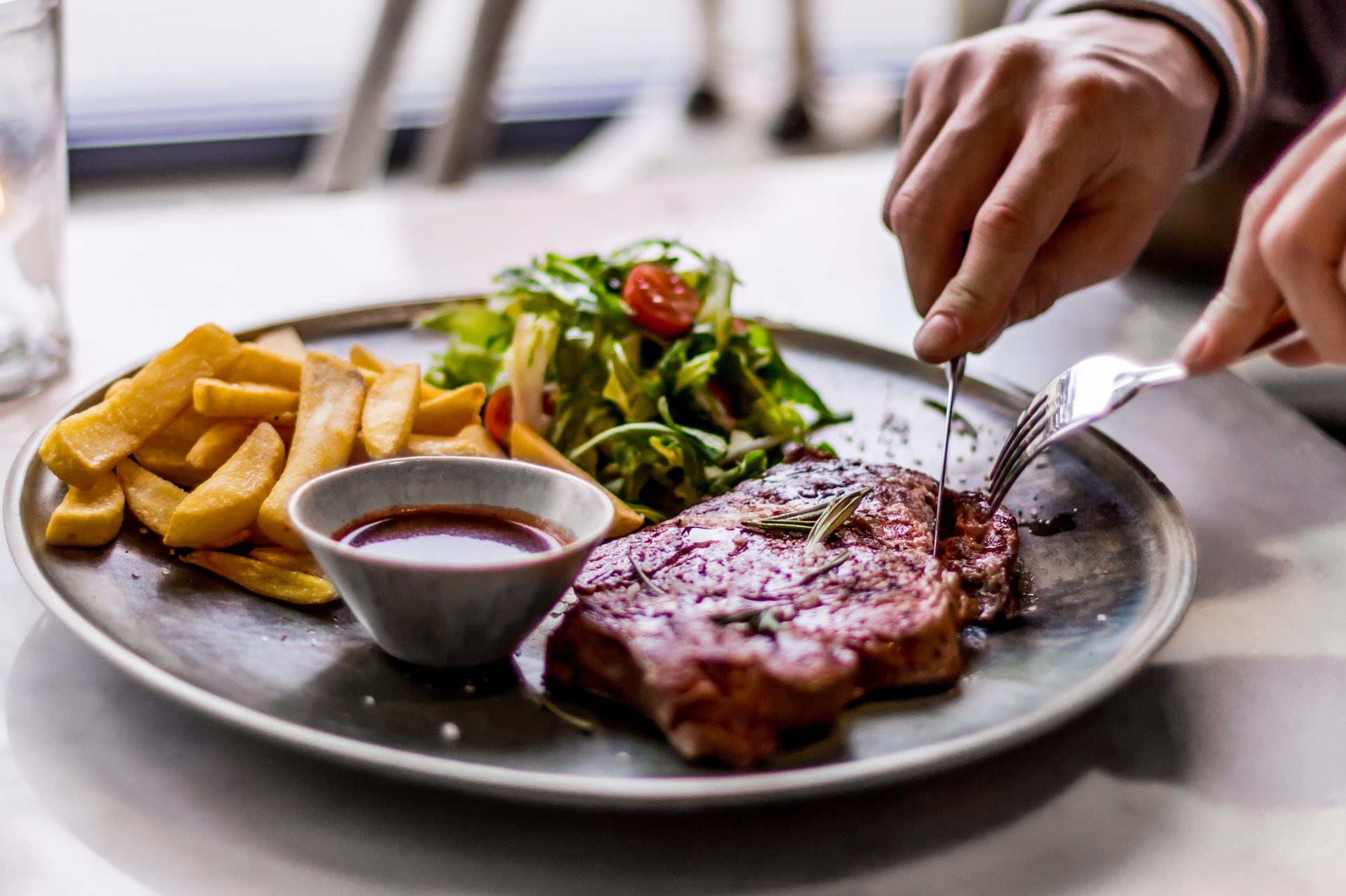 Close-Up Of Hands Cutting Into Steak Served On Plate With Fries